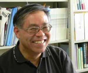 小野田の胸から上の写真。本棚の前で歯を見せて笑っている。