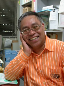 小野田の上半身の写真。夜の研究室で椅子に座り、右手で頬杖を軽くつきながら歯を見せて笑っている。
